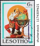 Small photo of Milan, Italy – July 28, 2018: Santa Claus studying globe by Norman Rockwell on stamp