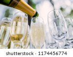 the waiter pours champagne in glasses on the street - wedding catering - look from below
