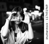 Young beautiful smiling Asian woman in street at night black and white, - stock photo