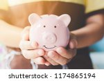 female hand holding piggy bank. ... | Shutterstock . vector #1174865194