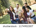 group of friends taking selfie... | Shutterstock . vector #1174902307