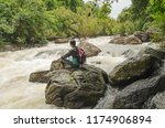 man on the rock at cataract in... | Shutterstock . vector #1174906894