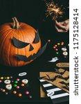 halloween preparation. hands... | Shutterstock . vector #1175128414