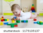 Small photo of Cute happy smiling baby playing with colorful rattle toys. New born child, little girl learning crawling. Family, new life, childhood, beginning concept. Baby learning grab wooden blocks.