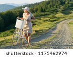 girl with a bicycle on a rural... | Shutterstock . vector #1175462974