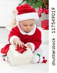 Baby girl in santa outfit opening a present sitting on the floor - stock photo