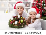Kids holding an advent wreath they decorated - proud of their work - stock photo