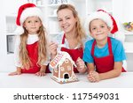 Family at christmas making a gingerbread cookie house together - stock photo