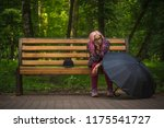 Small photo of symmetry autumn melancholy concept of alone sitting young sad girl on wooden bench with pink hair and classic black umbrella and hat in outdoor green park environment for walking