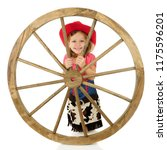 An adorable young cowgirl smiling from behind a large western wheel. Isolated on white. - stock photo