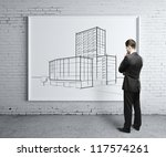 businessman looking at skyscraper on desk - stock photo