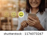 Small photo of Businesswoman pressing face emoticon on virtual touch screen at smartphone .Customer service evaluation concept.