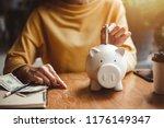 woman hand putting money bank... | Shutterstock . vector #1176149347