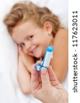 Little girl receiving homeopathic medication - hand with bottle and granules in foreground - stock photo