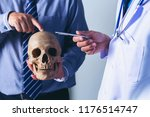 doctor is holding a human skull ... | Shutterstock . vector #1176514747