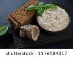 Stock photo close up of a bowl with vorschmack or forshmak made of herring fillet on a black wooden serving 1176584317