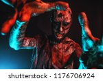 a scary zombie is touching a... | Shutterstock . vector #1176706924