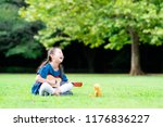 girl playing guitar to teddy... | Shutterstock . vector #1176836227