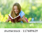 Small photo of Beautiful smiling teenage girl in blue blouse lying on grass and read book, against green of summer park.