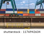 green crane loads over stacked... | Shutterstock . vector #1176942634