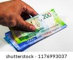 a bundle of money in his hand.... | Shutterstock . vector #1176993037