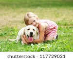 Stock photo a little blond girl with her pet dog outdooors in park 117729031