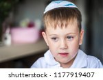 Small photo of A beautiful blue eyed Caucasian kid with a traditional Jewish kippah cap on his head. A Russian-speaking Jew in Israel portrait. Post-Soviet Jews make up over 15 per cent of Israeli society.