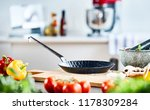Small photo of Small frying pan or skillet on a wooden chopping board surrounded with fresh salad ingredients and a pestle and mortar with herbs in a low angle view