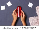 Stock photo an intimate lubricant in the hand against the background of the sheets and condoms 1178373367