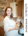 pregnant woman with salmon in the kitchen - stock photo