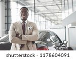 Young black businessman on auto salon background. Car sale and rent concept. - stock photo