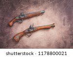 Two vintage pistols on wooden background, toned