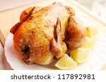 Ruddy roast chicken with lemon and spices - stock photo
