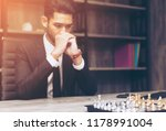 Small photo of Young Asian Businessman tries to cope with nervous tension or anxiety while play with chess game. start up business strategy and tactic concept