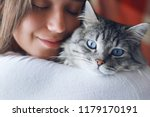 Stock photo woman at home in light room holding and hug her lovely fluffy cat gray tabby cute kitten with blue 1179170191
