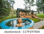 woman enjoys outdoor hot tub in ... | Shutterstock . vector #1179197404
