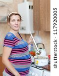 pregnant woman cooking dumplings in the pan on the stovetop - stock photo