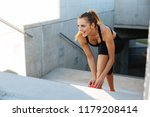 fit young woman tying her shoe... | Shutterstock . vector #1179208414