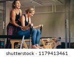 smiling woman at the gym doing... | Shutterstock . vector #1179413461