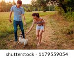 young couple walking pug dog in ... | Shutterstock . vector #1179559054