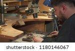 bearded jeweler directing the... | Shutterstock . vector #1180146067