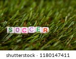 Small photo of The word soccer is made up of cubes with colored letters lying on an artificial green grass