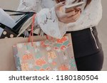 woman holding bags and mobile... | Shutterstock . vector #1180180504