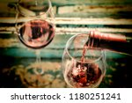 pouring wine into a glass.... | Shutterstock . vector #1180251241
