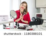 Small photo of Closeup photo of young beautiful European lady making video tutorial with beauty tips, reviewing different brushes for makeup that she is holding in hands, sharing professional opinion with viewers