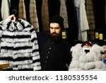 guy with beard chooses furry... | Shutterstock . vector #1180535554