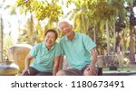 Stock photo asian elderly couple laugh together in green natural park background 1180673491