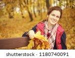 young beautiful woman in autumn ... | Shutterstock . vector #1180740091