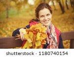 young beautiful woman in autumn ... | Shutterstock . vector #1180740154