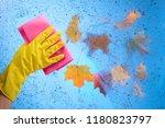 hand in yellow rubber glove... | Shutterstock . vector #1180823797